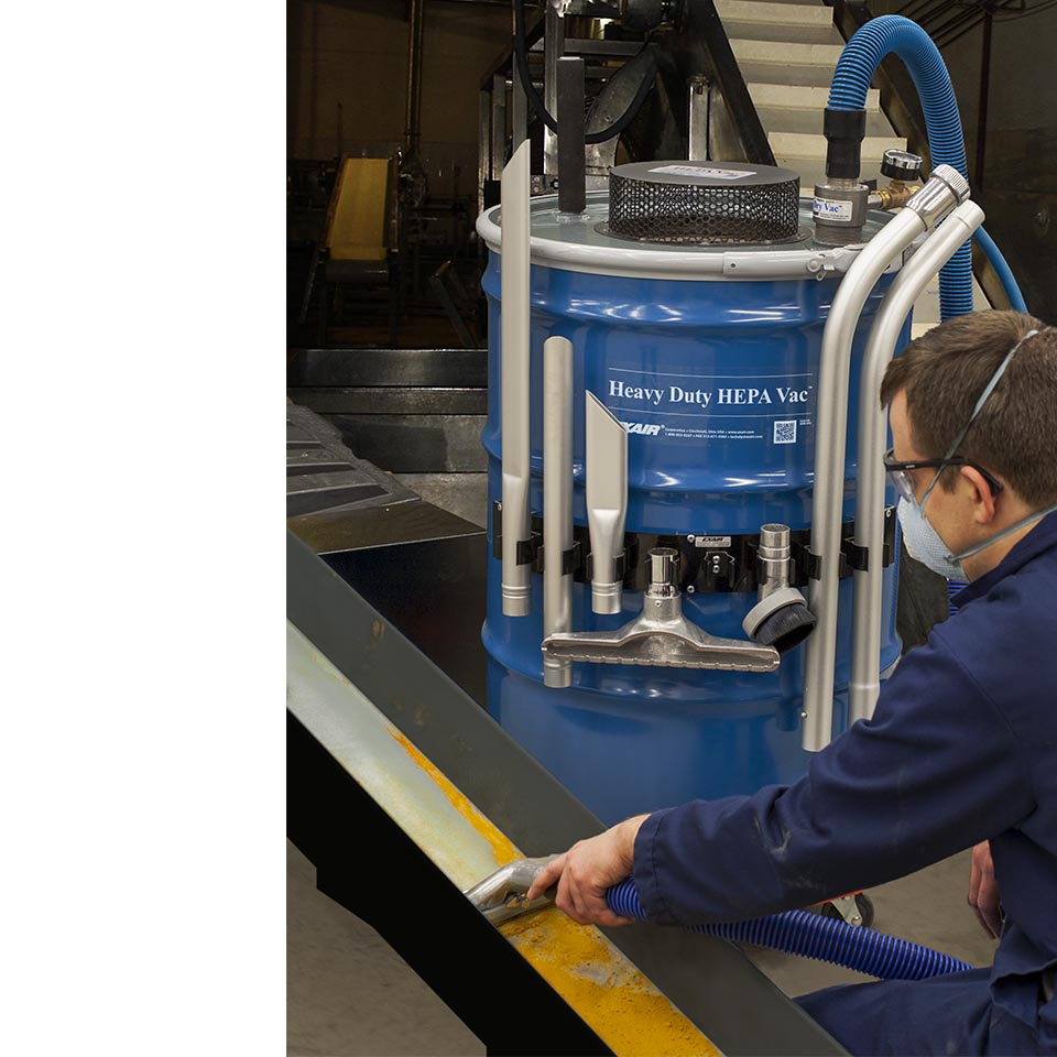 A technician uses a Heavy Duty HEPA Vac to perform scfheduled maintenance on a pulverizer.