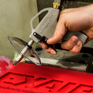 Here, a VariBlast Compact Safety Air Gun is used to blow off plastic shavings from a CNC operation.